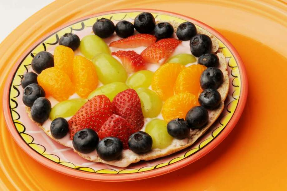 Make breakfast fun by serving fruizza: a pita-based pizza topped with yogurt, grapes, strawberries and more. (Luanne M. Ferris / Times Union) Photo: LUANNE M. FERRIS / 00008243A