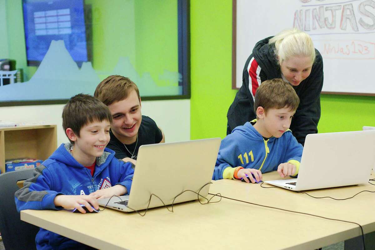 Angelle Bullard watches as her sons Jake Bellard and Connor Bellard learn about developing computer games and mobile apps with the help or Code Ninjas lead sensei Tanner Blackard at the company's Pearland facility
