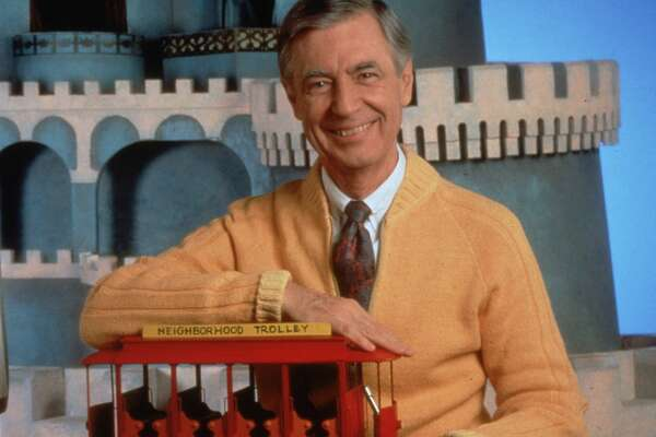 circa 1985:  Portrait of children's television personality Fred Rogers (1928 - 2003) smiling whilst posing with a toy trolley on the set of his public television show, 'Mister Rogers' Neighborhood'.