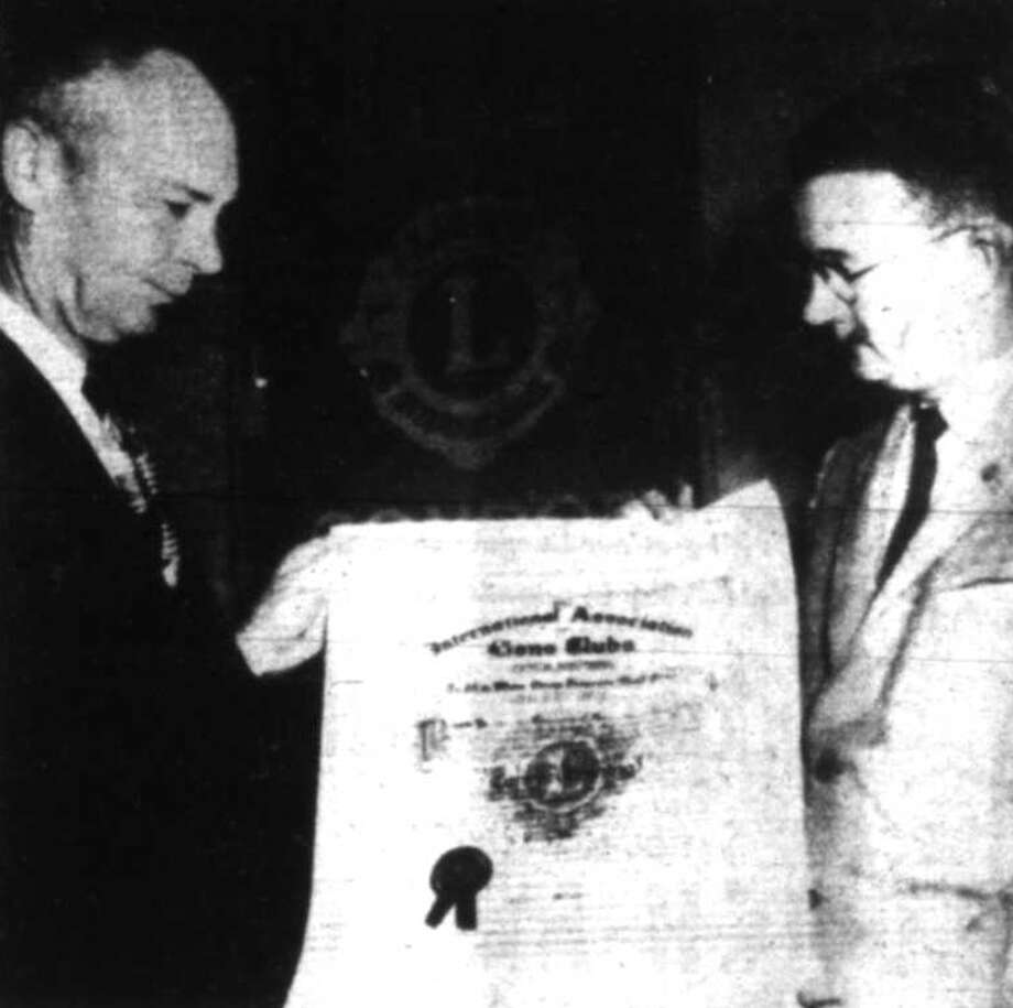 Frank Zachry, left, first president of the Conroe Evening Lions Club, is presented a charter for the group by Robert Lundy, Lions Club International District Governor on Jan. 30, 1958.