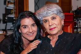 """A senior hispanic lady with silver hair is seen with her niece in a moment of Latin togetherness and love. The niece's expression says, """"I am with my favourite aunt."""" Photo shot indoors, in an apartment in Bogota. They are all smiles. Horizontal format."""