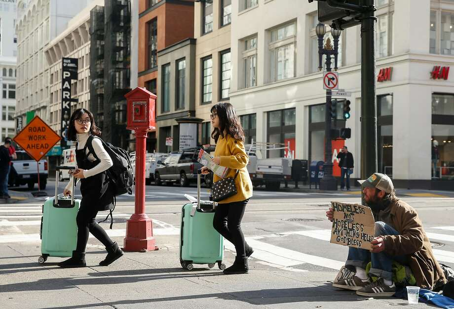 Two women wheel bags past Abram Lange, a homeless man originally from Eugene, Ore., at Powell and O'Farrell streets. Photo: Jessica Christian, The Chronicle