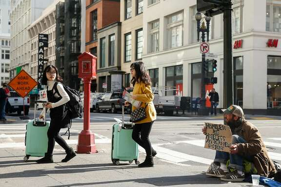 Two women with suitcases walk past Abram Lange, a homeless man originally from Eugene, Oregon, on the corner of Powell and O'Farrell streets Tuesday, Jan. 23, 2018 in San Francisco, Calif.