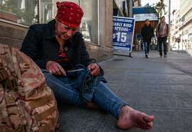 Amy, a homeless woman, works on repairing her jeans while standing near Mason and Post streets Tuesday, Jan. 23, 2018 in San Francisco, Calif.