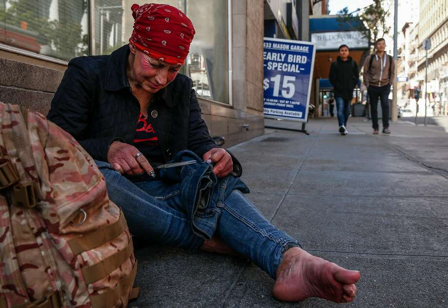 Amy works on repairing her jeans at her perch near the corner of Mason and Post, close to Union Square. Photo: Jessica Christian, The Chronicle