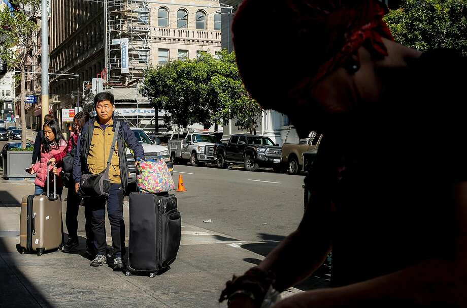 Tourists with suitcases walk past Amy, a homeless woman, as she organizes her bag while hovering near Mason and Post streets. Photo: Jessica Christian, The Chronicle