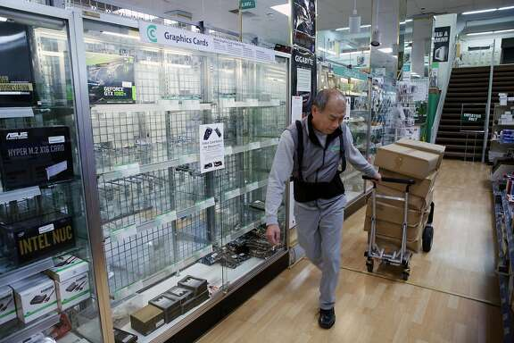 Sam Duong moves boxes to stock the store at Central Computers, Thursday, Jan. 25, 2018, in San Francisco, Calif. Cryptocurrency miners are buying out all the high-end graphics processor units they can find, which is driving the prices up and causing supply shortages at stores like Central Computers. A single unit was on display, an EVGA GeForce GTX 1080 Ti SC for $1,059.95.