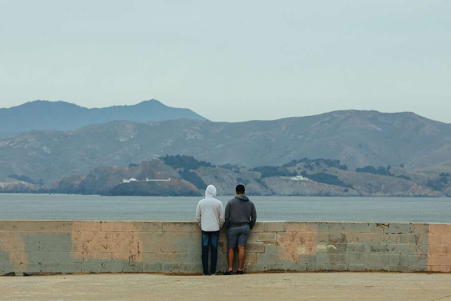 A couple watches the waves at Lands End in San Francisco. Little rain is on the horizon for the Bay Area, nor snow for the Sierra. Photo: Mason Trinca, Special To The Chronicle