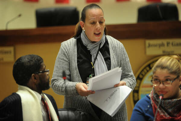 Brridgeport City Council member Eneida Martinez looks at exhibits from a presentation by the city attorney over how sewer use bills are collected during a Bridgeport City Council meeting at City Hall in Bridgeport, Conn. on Monday, January 29, 2018. At left is Councilman Ernest Newton and at right is Council President Aidee Nieves.