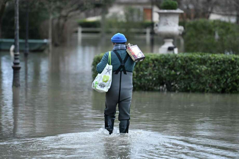 On Monday, a local resident wearing waterproof pants carries boxed wine down a flooded street near the Seine Siver in Villennes-sur-Seine, west of Paris. Photo: STEPHANE DE SAKUTIN, Contributor / AFP or licensors