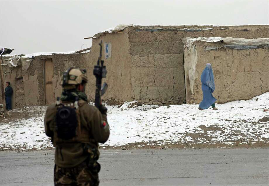 An Afghan woman leaves the site of an attack at the Marshal Fahim academy in Kabul, Afghanistan Monday, Jan. 29, 2018. Islamic State militants attacked Afghan soldiers guarding the military academy in the capital Kabul on Monday, killing at least 10 troops and wounding 16. AP Photo/Rahmat Gul) Photo: Rahmat Gul, STF / Copyright 2018 The Associated Press. All rights reserved.