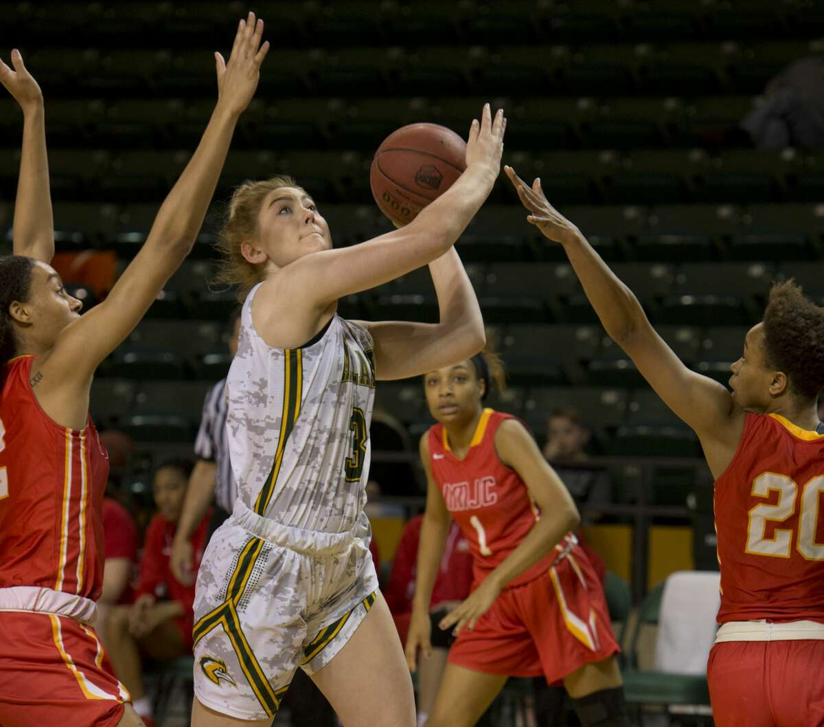 Midland College's Bianca Thacker drives through the lane as New Mexico Junior College's Alexes Bryant and Tatiana Wright try to block her 01/29/18 at the Chaparral Center. Tim Fischer/Reporter-Telegram