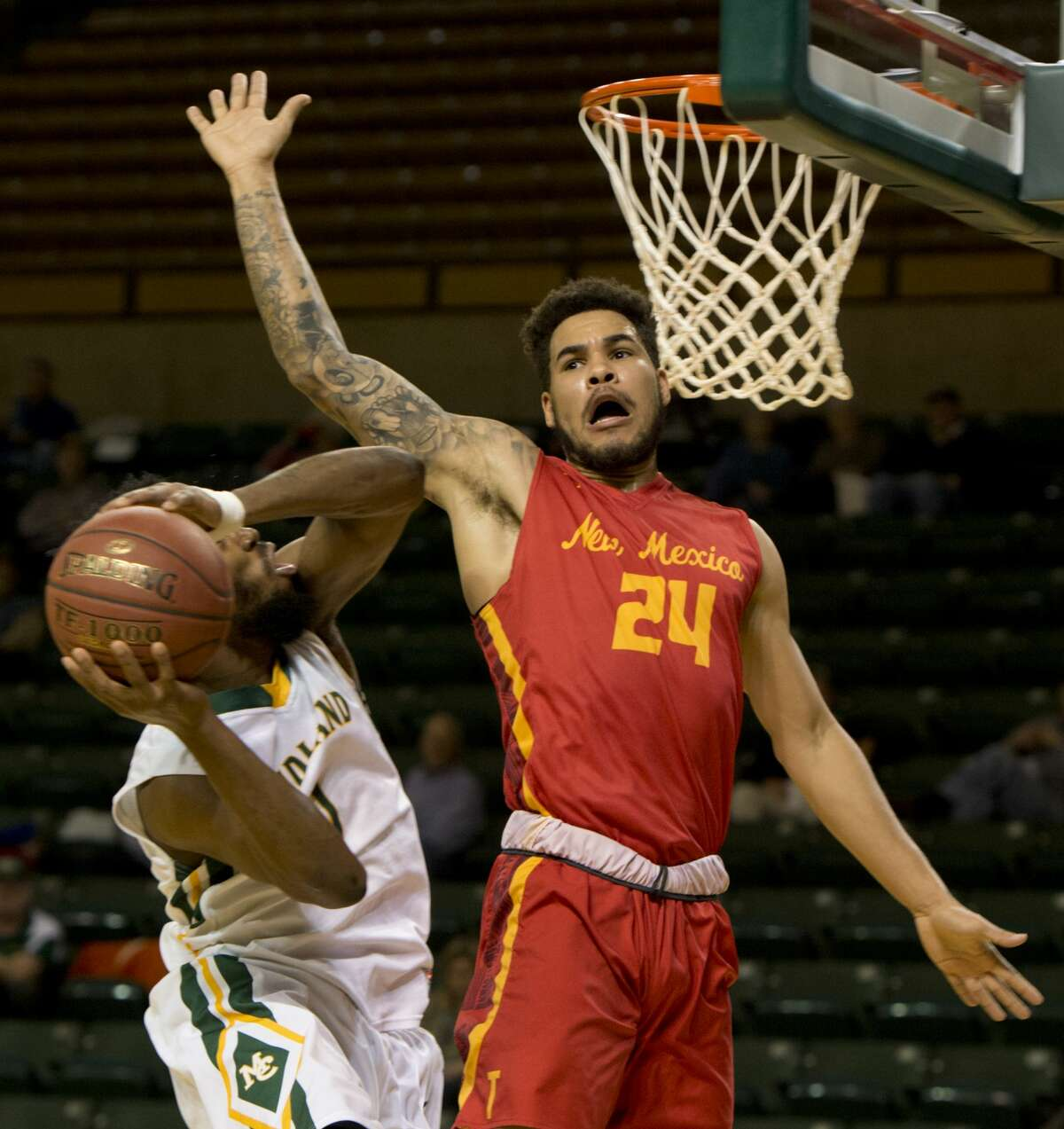 Midland College's Marquell Fraser tries to put a shot up as New Mexico Junior College's Jacob Bodin defends 01/29/18 at the Chaparral Center. Tim Fischer/Reporter-Telegram