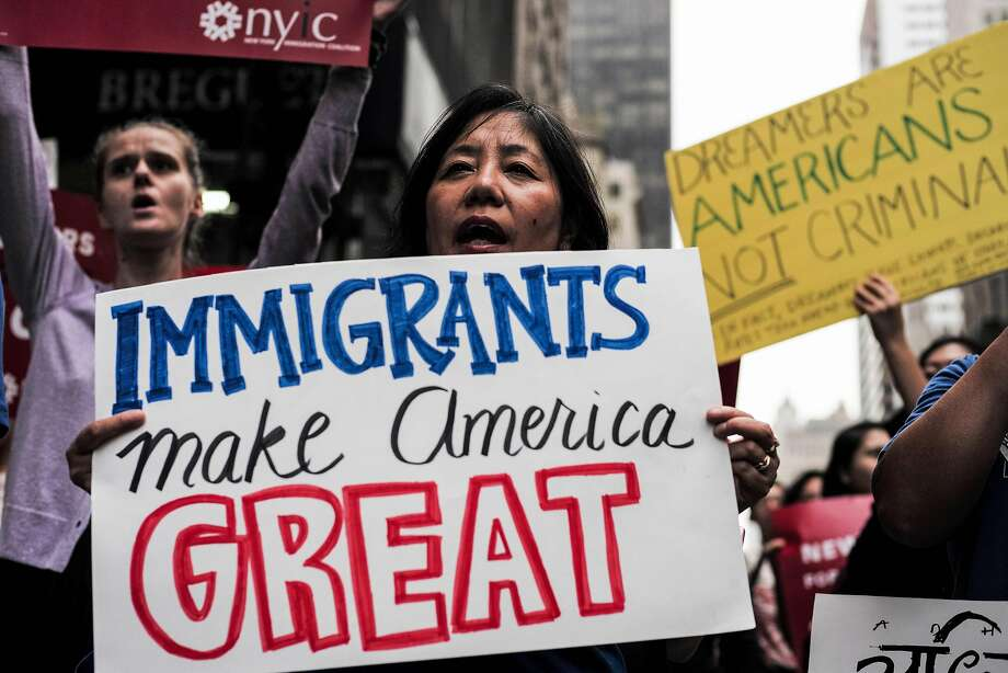 """(FILES) This file photo taken on October 5, 2017 shows protesters during a demonstration against US President Donald Trump during a rally in support of the Deferred Action for Childhood Arrivals (DACA), also known as Dream Act, near the Trump Tower in New York. US President Donald Trump's administration has unveiled a sweeping new immigration plan to Congress that offers 1.8 million young unauthorized immigrants known as """"Dreamers"""" a path to citizenship over 10-12 years.In a comprehensive reform that will be formally presented next week, Trump also asked Congress on January 25, 2018 to eliminate the popular """"green card lottery"""" program and severely restrict family immigration, steps analysts say could cut in half the more than one million foreign-born people moving to the country annually.  / AFP PHOTO / Jewel SAMADJEWEL SAMAD/AFP/Getty Images Photo: JEWEL SAMAD, AFP/Getty Images"""