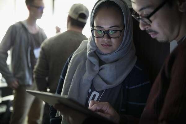Female hacker in hijab working with teammate at hackathon using digital tablet