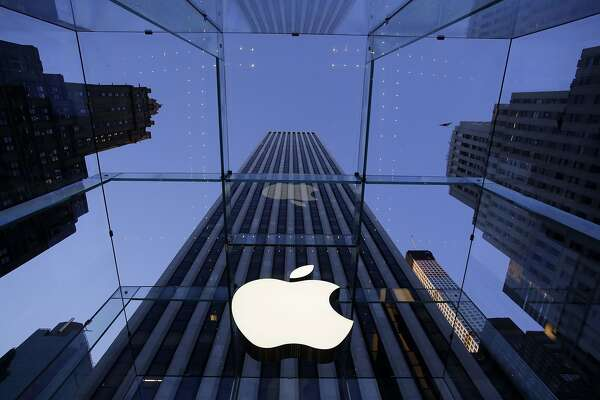 FILE - In this Sept. 5, 2014, file photo, the Apple logo hangs in the glass box entrance to the company's Fifth Avenue store in New York.  Companies like Apple and Walt Disney as well as Walmart's philanthropic foundation are investors in a $23 million venture fund aiming to use tools like artificial intelligence and blockchain technology to improve global labor practices. Working Capital was launched Tuesday, Jan. 30, 2018  by Humanity United, a foundation that's part of the Omidyar Group started by the founder of eBay, Pierre Omidyar. (AP Photo/Mark Lennihan, File)