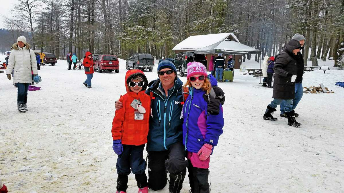 """Brian Talon of Southington attends an ice-sculpting workshop with daughters Emma and Lily at the 2015 """"No Child Left Inside"""" winter festival at Burr Pond State Park in Torrington."""