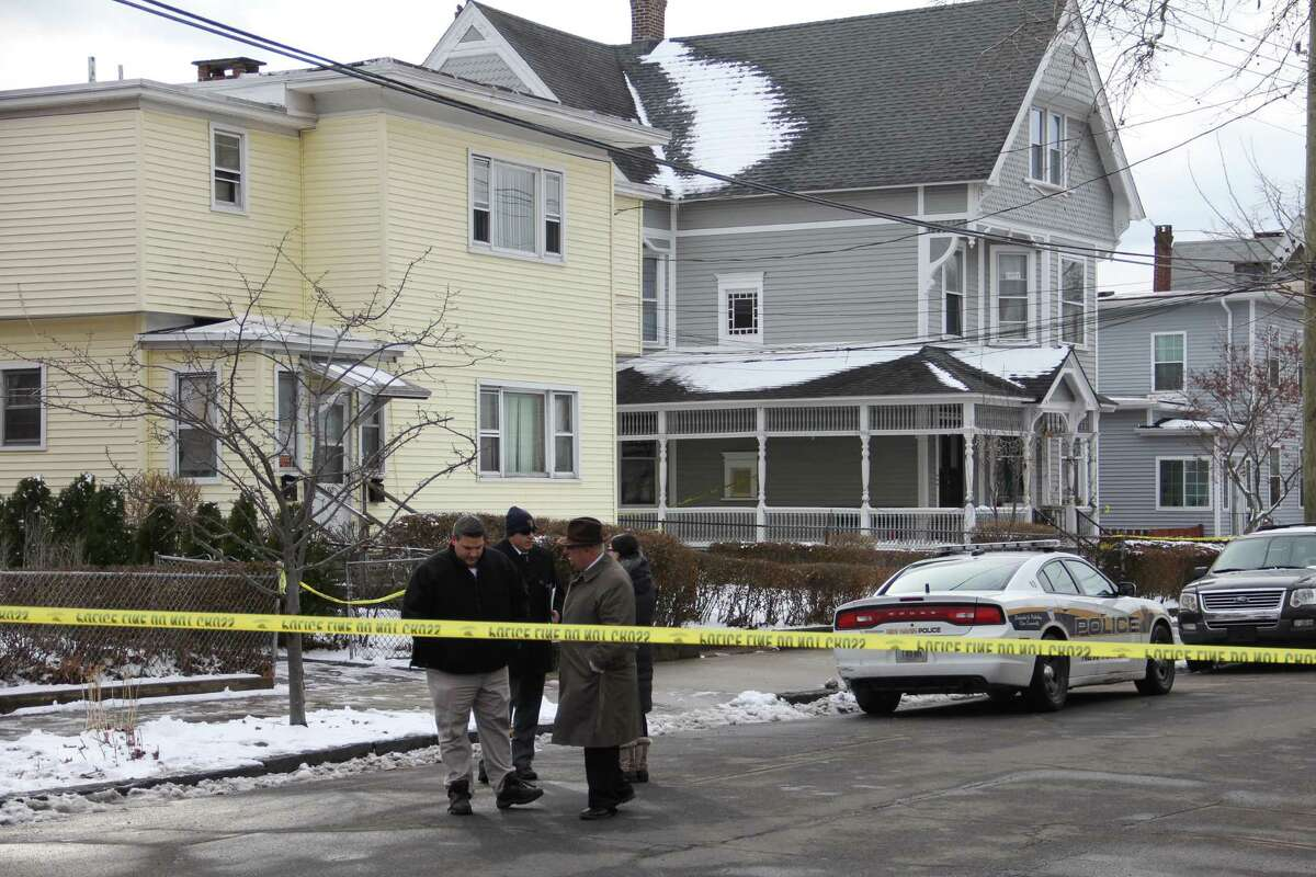 New Haven police stand outside the residence at 180 Exchange St., where a woman's body was found Tuesday.