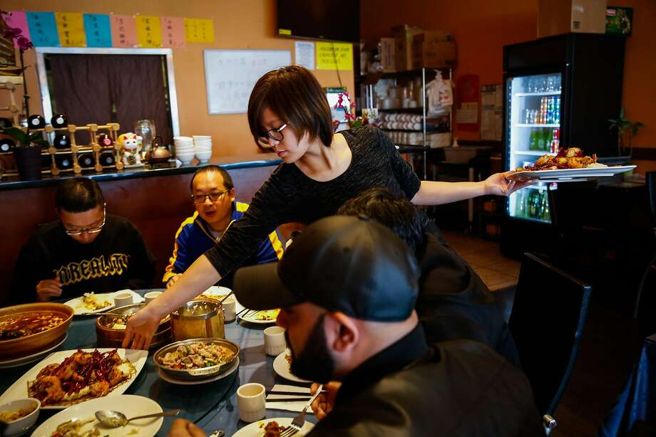 Waitress Qian Long (center) serves dishes at Chef Zhao Bistro in San Mateo. Photo: Gabrielle Lurie, The Chronicle