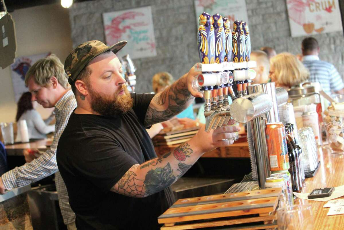 A bartender serves a beer at Stony Creek Brewery in Branford, Conn. on July 7, 2017.