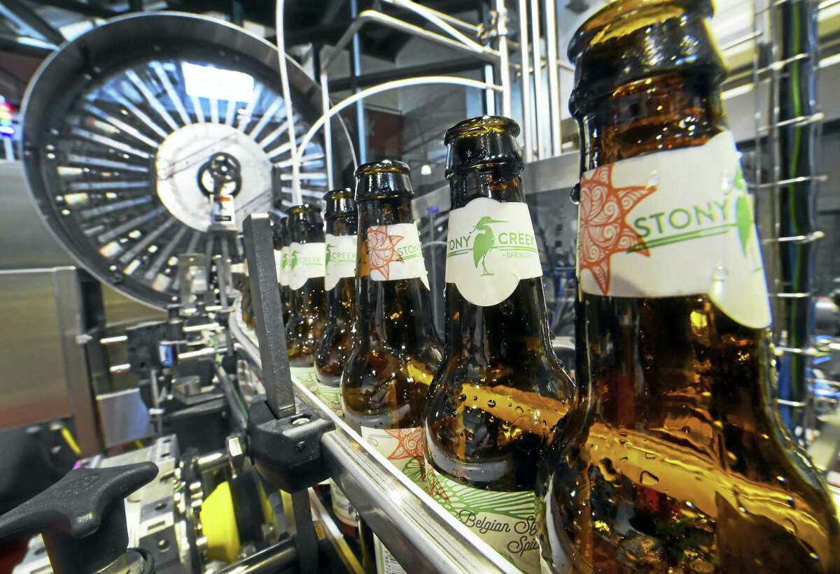 (Peter Hvizdak - New Haven Register) ¬ The Stony Creek Brewery bottle line that labels, dates, rinses, fills and caps beer as part of the bottling and packaging process on a conveyor in the 30,000square-foot facility at the Branford, ConnecticutWednesday, May 20, 2015.