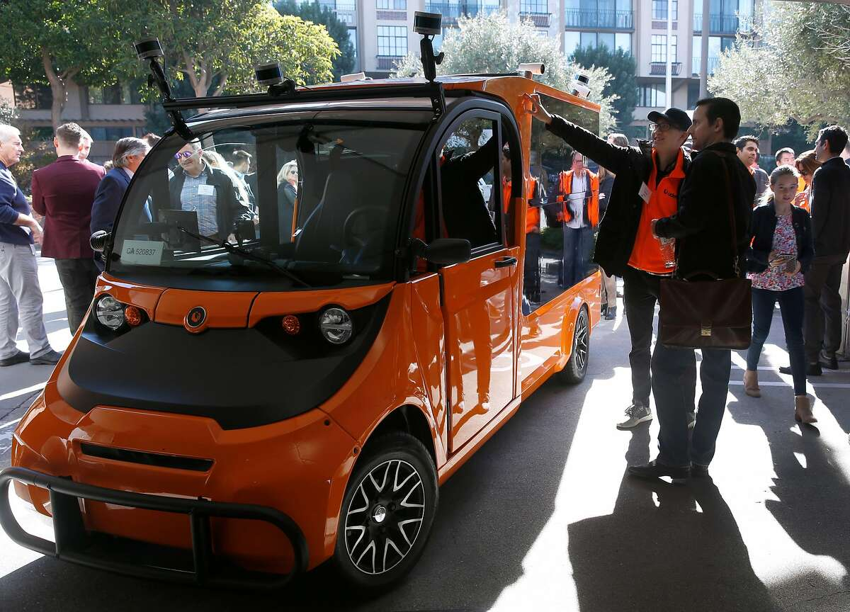 Yunong Jiang (left) and Nick Degnan look at an autonomous grocery delivery van unveiled by Udelv in San Mateo, Calif. on Tuesday, Jan. 30, 2018. Jiang is a mechanical engineer for Udelv and Degnan works for Motivo Engineering, which developed the locker system in the rear of the van.