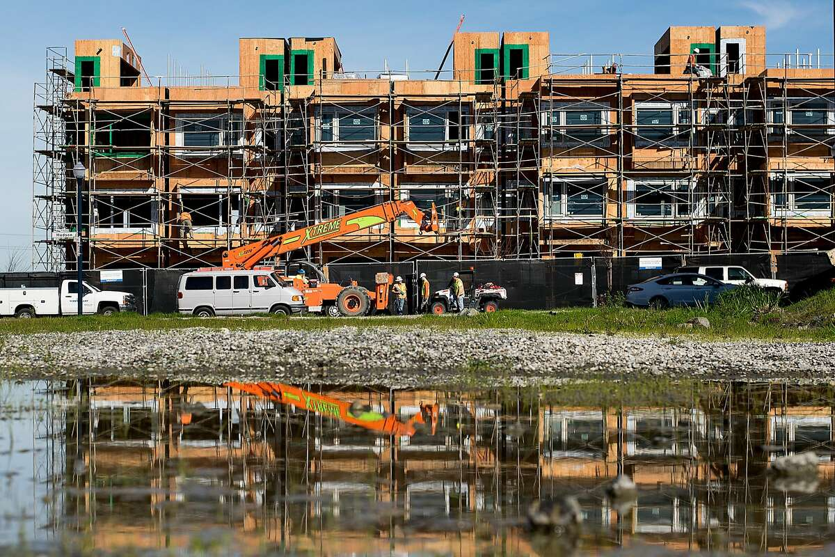 Construction workers build new housing at the former Hunters Point Naval Shipyard in San Francisco.