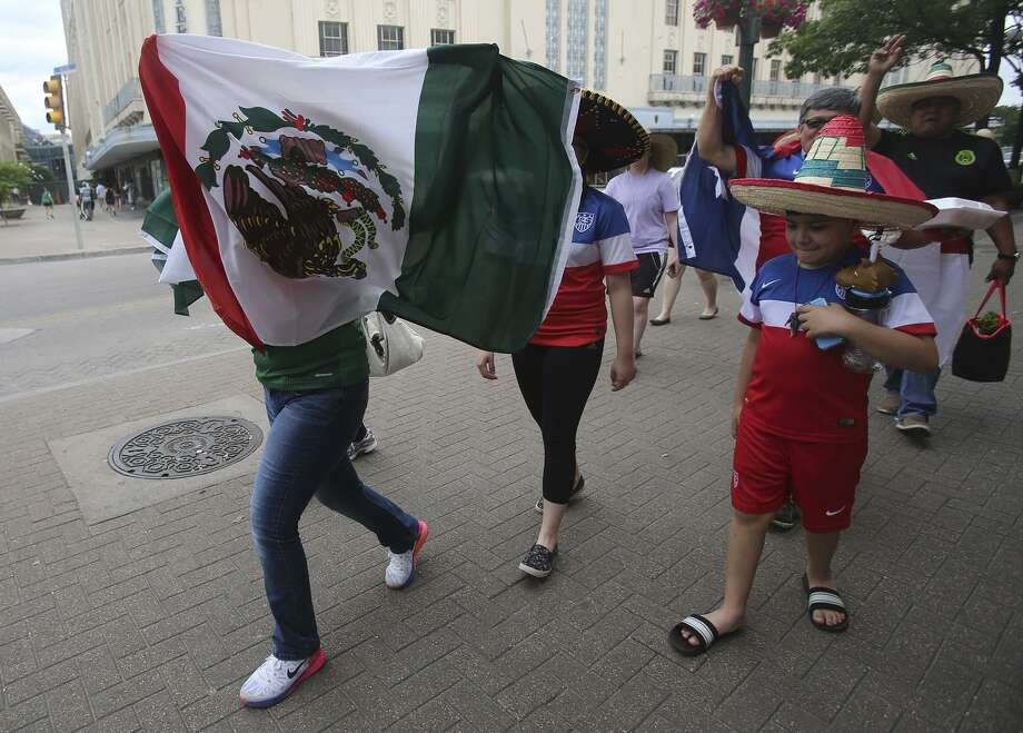 Soccer fans walk in Alamo Plaza Wednesday April 15, 2015 in anticipation of the match between the United States and Mexico's men's national soccer teams to be held at the Alamodome. Leading the charge with the Mexican flag (left) is Arlette Barajas,11, who was with her dad Julio Barajas. The family came from McAllen to see the soccer match. Photo: John Davenport, Staff / San Antonio Express-News / ©San Antonio Express-News/John Davenport