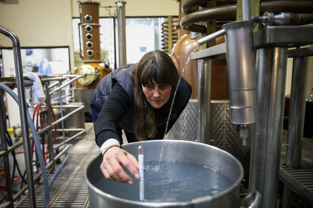 Lead distiller Kendra Scott measures the alcohol content of whiskey while working in the production area at Anchor Distilling in San Francisco, California, on Monday, Jan. 29, 2018.