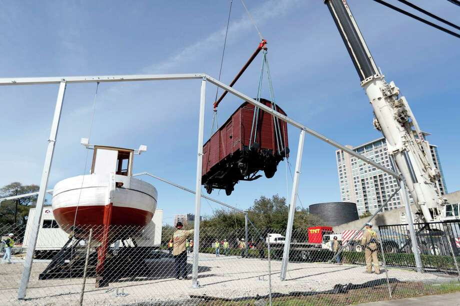 """One of the Holocaust Museum Houston's most iconic artifacts, the1942 World War II-era railcar, is moved to a temporary location by a crane, Tuesday, Jan. 30, 2018, in Houston. Holocaust Museum Houston relocated two of its most iconic artifacts, the railcar and the Danish Rescue Boat, in a crane """"flyover"""" to a lot adjacent to the Museum's main campus located at 5401 Caroline Street. The artifacts' relocation marks the beginning of construction to double the size of the Museum to 57,000 square feet of space, including expansion of the permanent exhibition space to allow the railcar and boat to be moved inside the new building for temperature-controlled preservation of the artifacts.  ( Karen Warren / Houston Chronicle ) Photo: Karen Warren, Staff / © 2018 Houston Chronicle"""