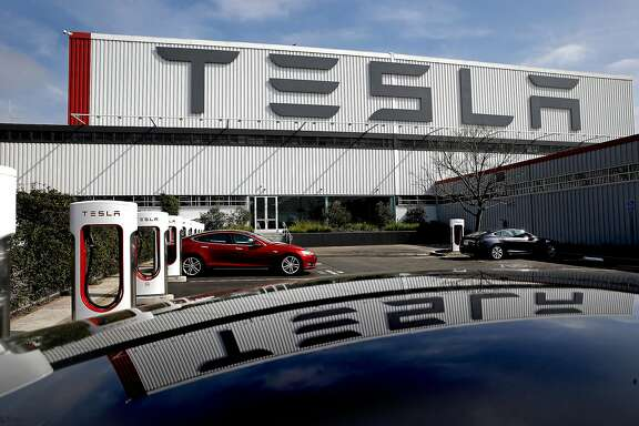 Tesla electric cars and charging stations are lined up outside the customer delivery center in front of Tesla Motors, California's only full-scale auto manufacturing plant, as seen on Thurs. Feb. 19, 2015,  in Fremont, Calif.