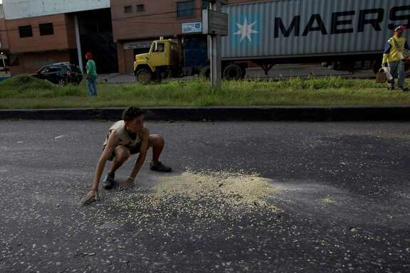 A youth moves to collect grains of corn on the street that fell from a truck that was looted outside the port in Puerto Cabello, Venezuela. Many are hungry in the country, and looting has increased.