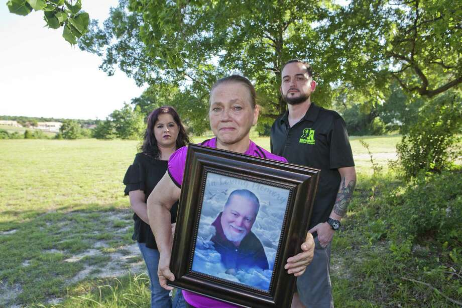 Shown are Stephanie Kingrey (from left), Sandra McCollum and Steve McCollum. Sandra McCollum holds a portrait of her late husband and their father, Larry McCollum, an inmate who died after arriving at the hospital with a body temperature of 109 degrees. Photo: Jose Yau /For The Houston Chronicle