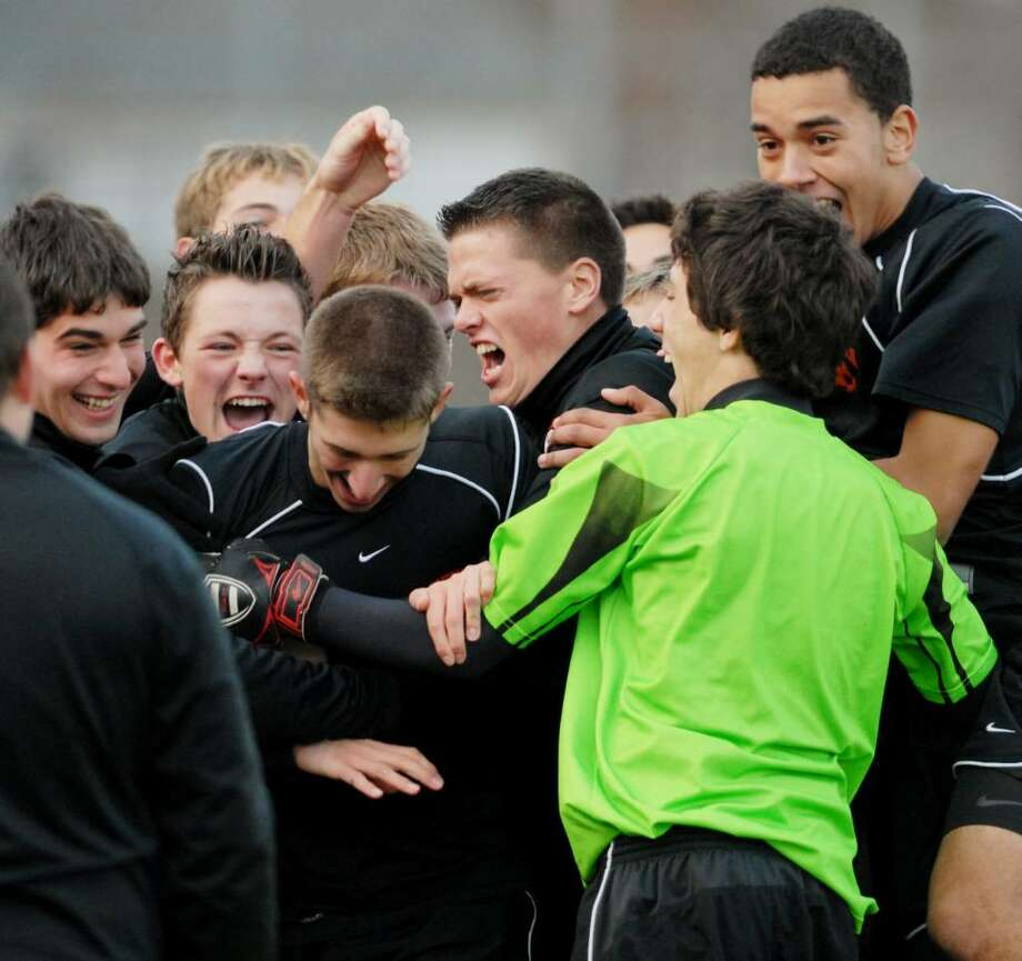 Mohonasen Boys Soccer player, Gianluca Puorto,  third from left, gets congratulated by teammates after he scored the only goal of the game, in sudden-death overtime, vs. Ichabod Crane in the Class A Soccer semifinals at Queensbury High School on Thursday, Nov. 5, 2009.   (Luanne M. Ferris / Times Union) Photo: LUANNE M. FERRIS / 00006242A