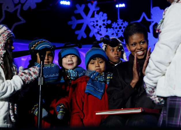 First lady Michelle Obama is pictured with children after reading them a story at the National Christmas Tree Lighting Ceremony which she attended with President Barack Obama, not pictured, in Washington, Thursday, Dec. 3, 2009. (AP Photo/Charles Dharapak) Photo: Charles Dharapak / AP