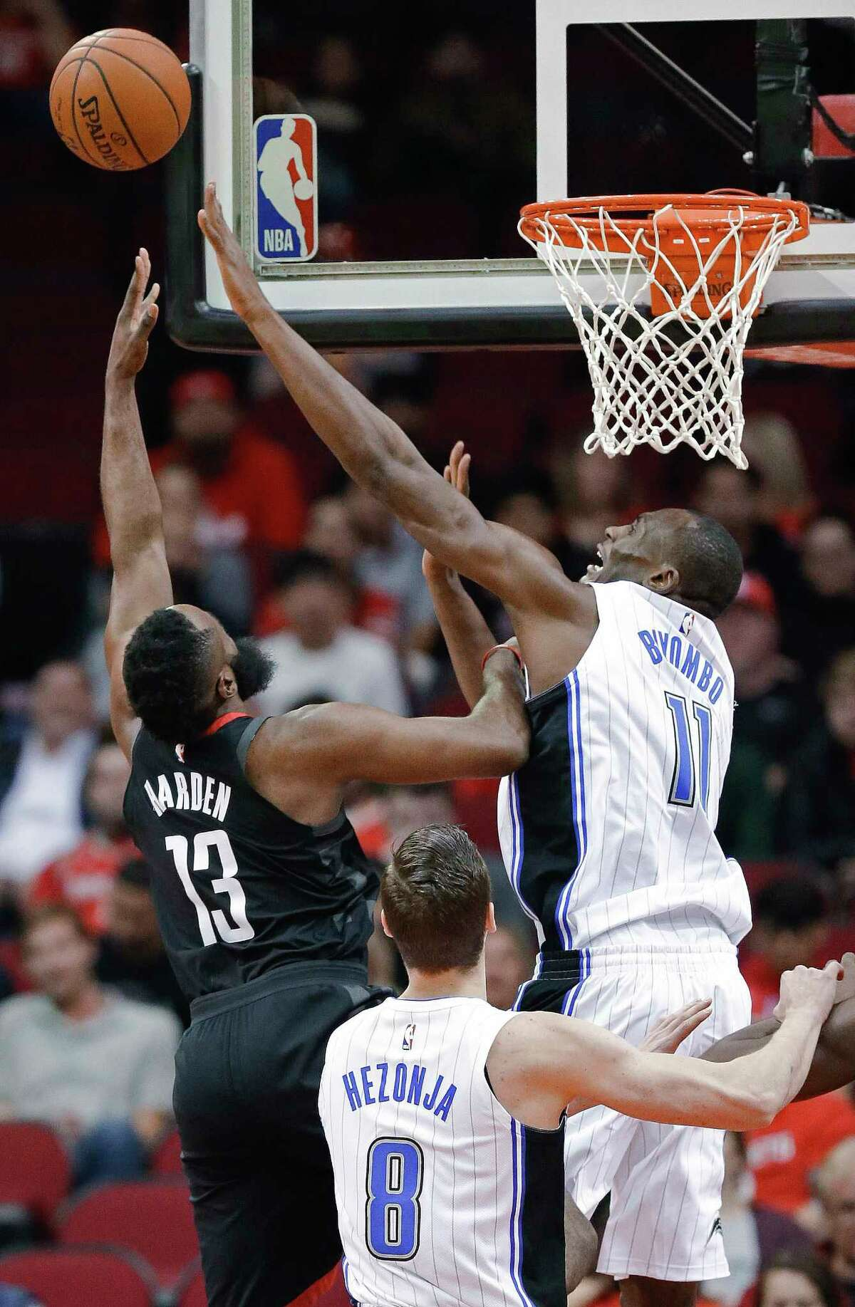 Houston Rockets guard James Harden (13) shoots as Orlando Magic center Bismack Biyombo, right, defends during the first half of an NBA basketball game Tuesday, Jan. 30, 2018, in Houston. (AP Photo/Eric Christian Smith)
