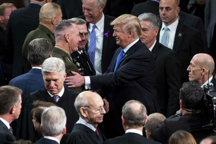 U.S. President Donald Trump (center right) greets Gen. Joseph Dunford (center left), chairman of the Joint Chiefs of Staff, after the State of the Union address.