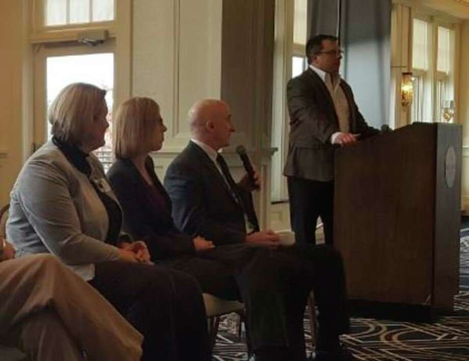 Kathy Dollard, director of behavioral health for MidMichigan Health, Kathryn Tate, community integration leader at The Legacy Center for Community Success and Midland Police Chief Clifford Block listen to Robert Kuzel, M.D. and president of the Midland County Medical Society, speak at a community symposium on the opioid crisis Thursday at the Midland Country Club.