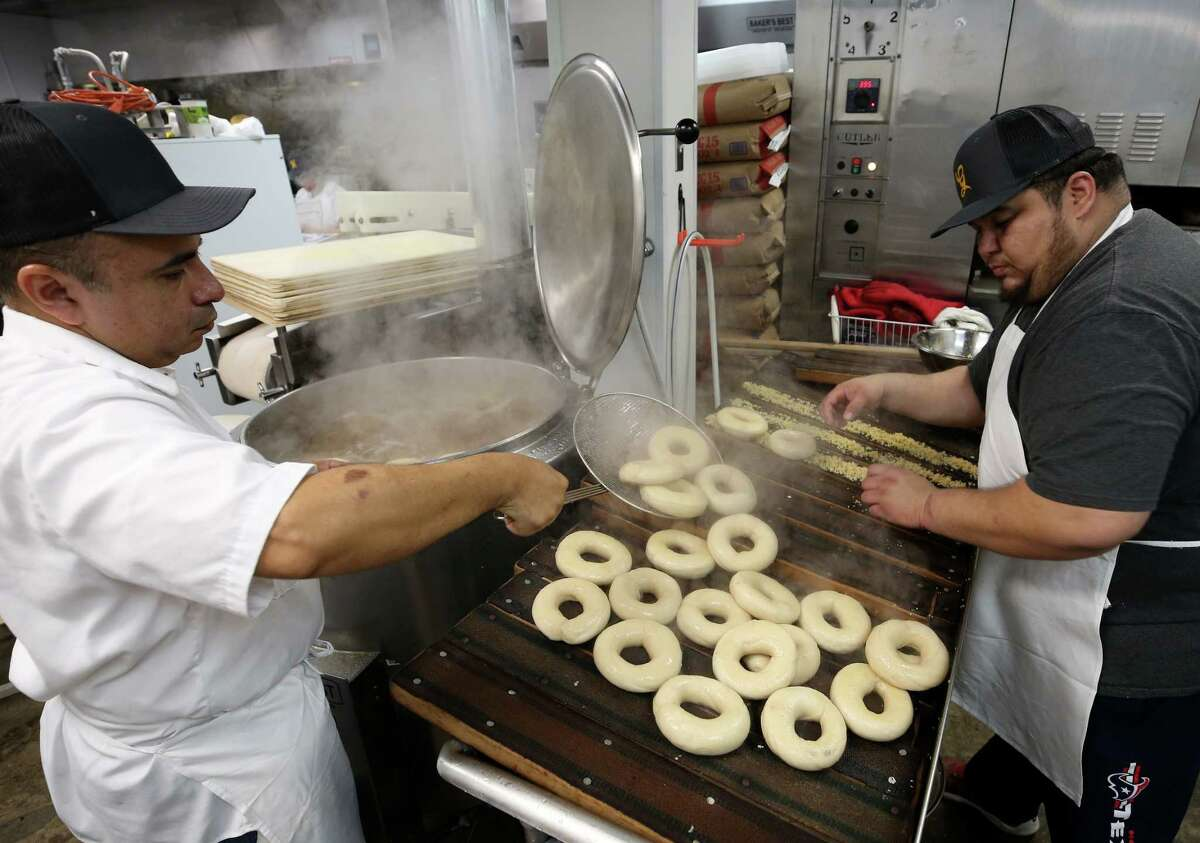 Head Baker Eliu Palacios, left, transfers a batch of freshly-boiled dough for baker Hugo Ayala to put in the oven at Golden Bagels & Coffee Friday, Jan. 26, 2018, in Houston.