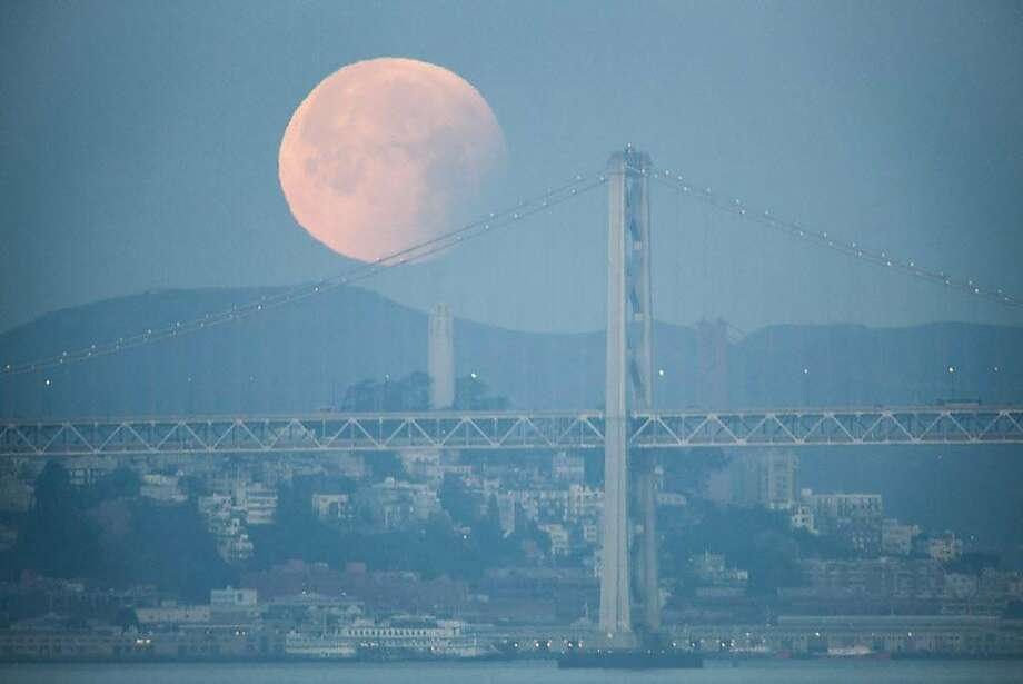 The Super Blue Blood Moon after the lunar eclipse sets behind the San Fancisco-Oakland Bay Bridge and Cost Tower as seen from the aircraft carrier USS Hornet in the early hours on Wednesday 31 January 2018 in Alameda, CA. Photo: Peter DaSilva