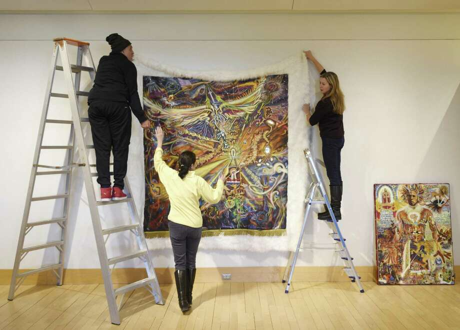 "Artist Paul Deo sets up his piece ""Algorithms of Ali"" with curator Ruth Sutcliffe-Heagney, center, and assistant curator Isabelle Schiavi at the Beyond Street Art exhibition at Greenwich Library's Flinn Gallery in Greenwich, Conn. Thursday, Jan. 25, 2018. Opening February 1, Beyond Street Art showcases the work of five street artists - Paul Deo, Billy the Artist, Blake Jamieson, Lady Pink, and Swoon. Photo: Tyler Sizemore / Hearst Connecticut Media / Greenwich Time"