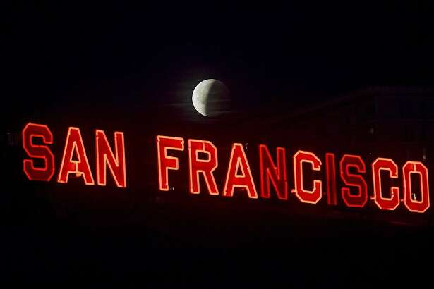 A partially-eclipsed super blue blood moon sets behind a sign at San Francisco's Ferry Building on Wednesday, Jan. 31, 2018. It's the first time in 35 years a blue moon has synced up with a supermoon and a total lunar eclipse, also called a blood moon because of its red hue. (AP Photo/Noah Berger)