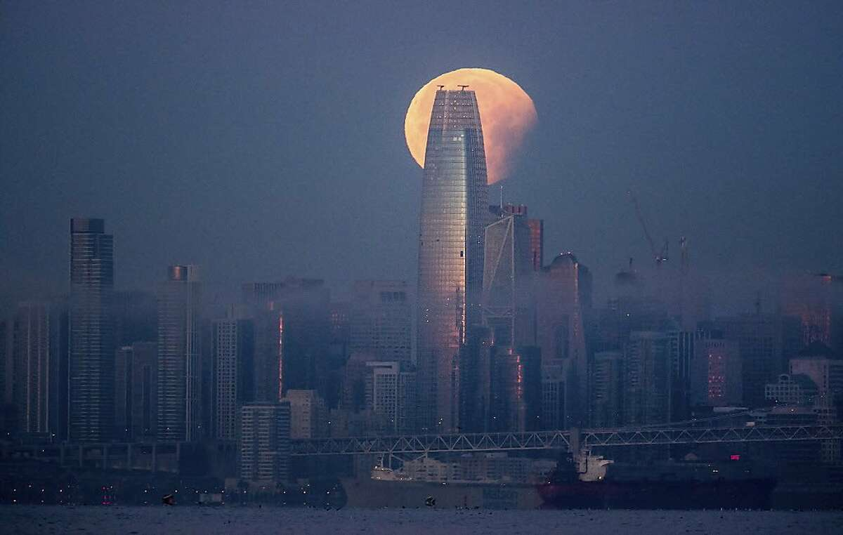 A partially-eclipsed super blue blood moon sets behind the Salesforce Tower on Wednesday, Jan. 31, 2018, in San Francisco. It's the first time in 35 years a blue moon has synced up with a supermoon and a total lunar eclipse, also called a blood moon because of its red hue.