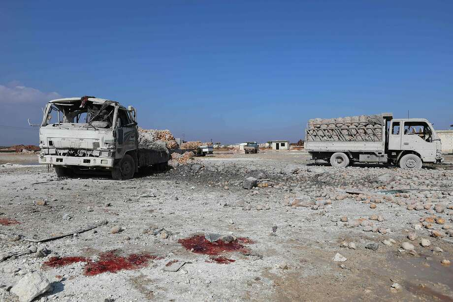 A picture taken on January 29, 2018 shows blood stains on the ground next to trucks loaded with sacks of potatoes standing abandoned after their windows were blasted from their frames following airstrikes by government forces which hit the vegetable market of the town of Saraqeb in Syria's northwestern province of Idlib. Syrian troops had been advancing on Idlib as part of a fierce offensive launched in late December with Russian backing.  / AFP PHOTO / OMAR HAJ KADOUROMAR HAJ KADOUR/AFP/Getty Images Photo: OMAR HAJ KADOUR, AFP/Getty Images