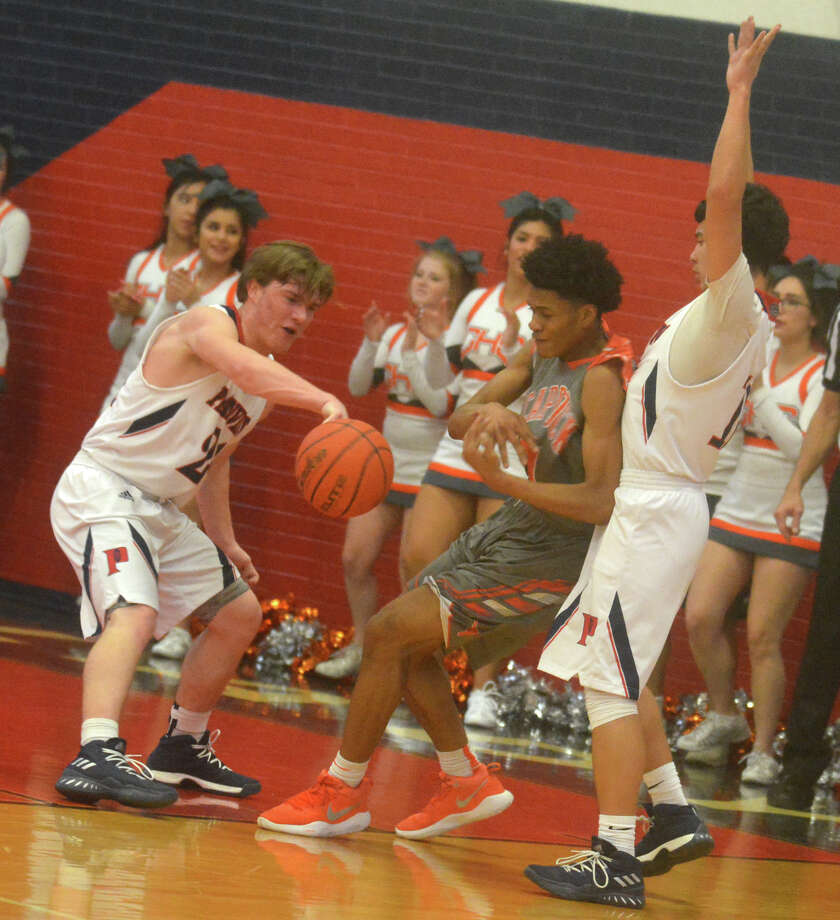 Plainview's Carson Hauk, left, slaps the ball away from a Caprock player as teammate Adrian Hinojosa, right, blocks the opponent's path to the basket during a District 3-5A game at the Dog House Tuesday night. Photo: Skip Leon/Plainview Herald