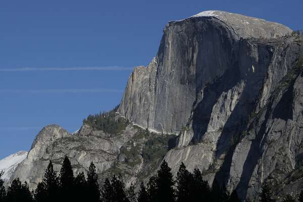 Classic late fall photo of Half Dome in Yosemite Valley, with cobalt blue sky and first touch of snow