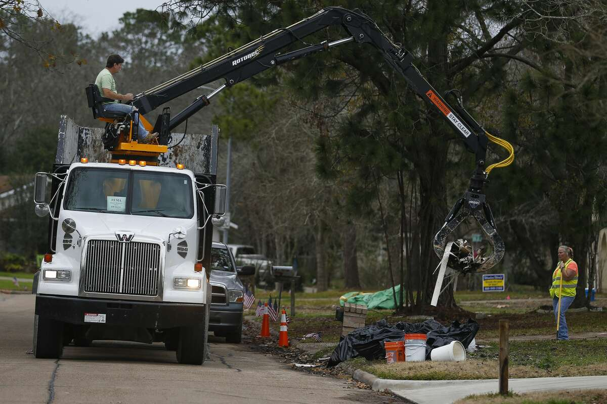 A FEMA disaster recovery vehicle picks up flood debris from a home in the Forest Bend neighborhood Thursday, Jan. 11, 2018 in Friendswood. The city of Friendswood has reverted from 2007 flood maps to 1999 maps to allow homeowners that were flooded during Hurricane Harvey to rebuild without mandating expensive home elevation requirements. ( Michael Ciaglo / Houston Chronicle)