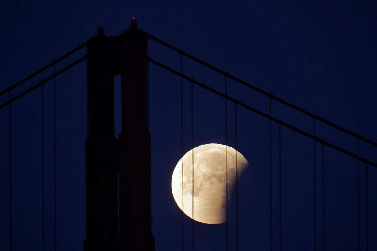 The partially-eclipsed Super Blue Blood Moon makes its way past the Golden Gate Bridge as seen from the San Francisco Yacht Club photograph it in San Francisco, Calif., on Wednesday, January 31, 2018.
