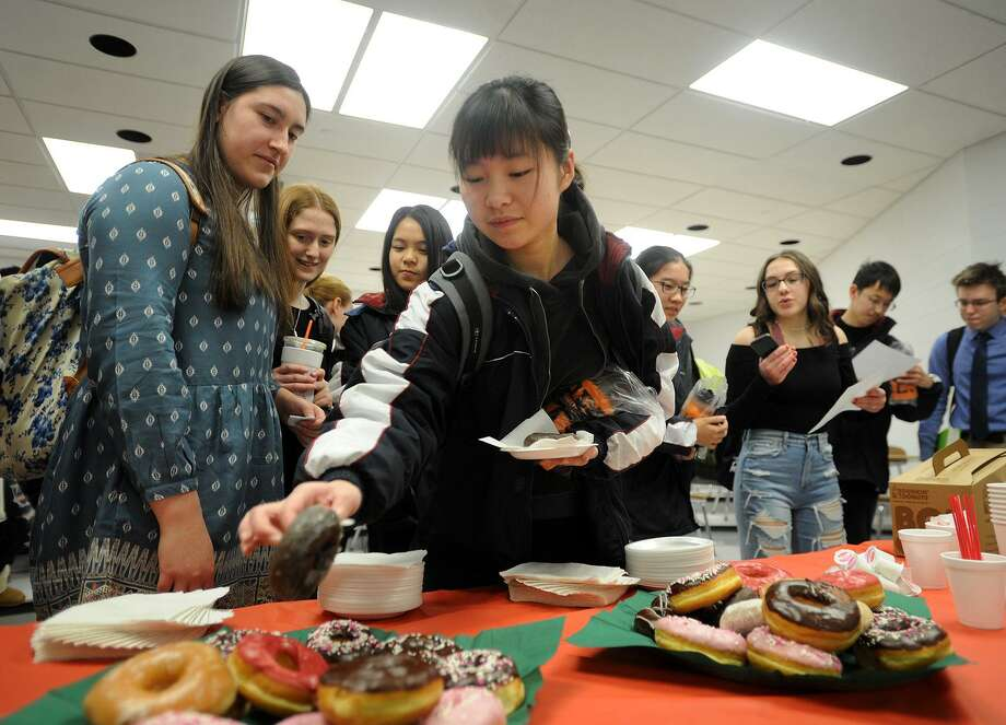 Wendy Yang, 16, tries a doughnut for the first time during a visit by high school students from Shanghai, China to Shelton High School on Wednesday, January 31, 2018. At left is Shelton junior Natalie Klimaszewski, 16, who accompanied Yang for the day. Photo: Brian A. Pounds / Hearst Connecticut Media / Connecticut Post