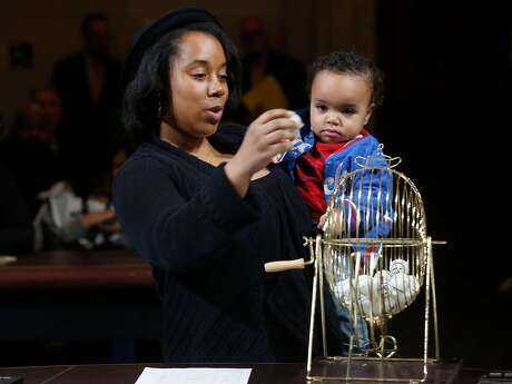 Tiffany Davis, with her son Isaiah Caraballo, drops a pingpong ball into the hopper before the permit winners are drawn. Photo: Paul Chinn, The Chronicle